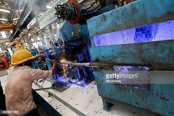 An employee clears debris from a pipemaking production line in the tube mill at the manufacturing facility of Uttam Galva Steels Ltd the Indian unit...