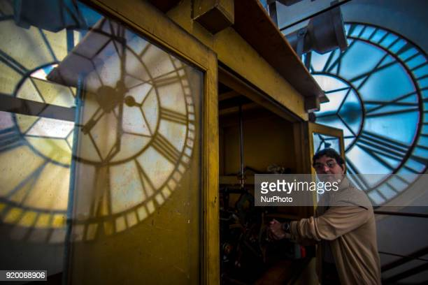 An employee climbs a ladder to check a huge clock on February 18 2018 in Luz Station in São Paulo Daylight saving time ends at 000 AM on Sunday when...