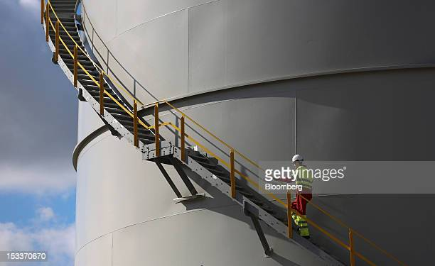 An employee climbs a staircase on the outside of a storage tank at the EON AG gas fired power station on the Isle of Grain UK on Thursday Oct 4 2012...