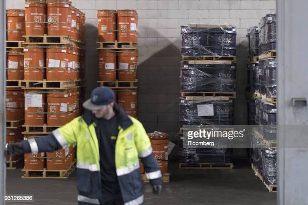 An employee closes the door as barrels of cobalt owned by Cobalt 27 Capital Corp stand beyond in Rotterdam Netherlands on Monday Jan 22 2018 Cobalt...