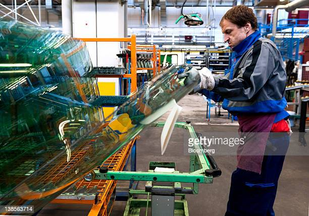 An employee collects a glass windscreen for a truck during the production process at the MercedesBenz plant in Woerth Germany on Wednesday Feb 8 2012...