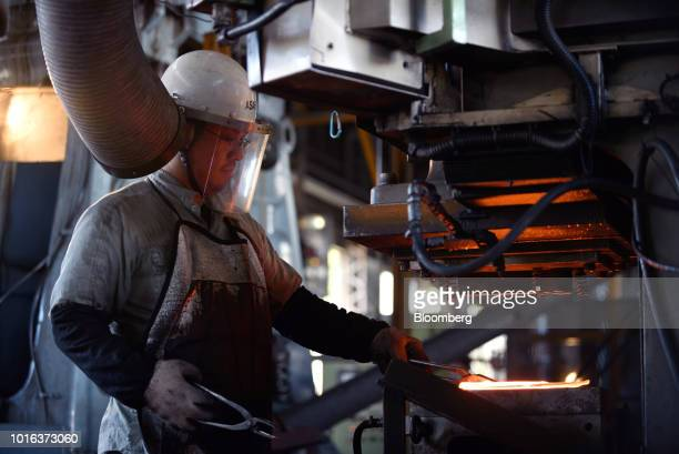 An employee collects a molten vehicle part from a mold at an Asahi Tekko Co factory in Nishio Aichi Prefecture Japan on Wednesday Aug 1 2018 Japan's...