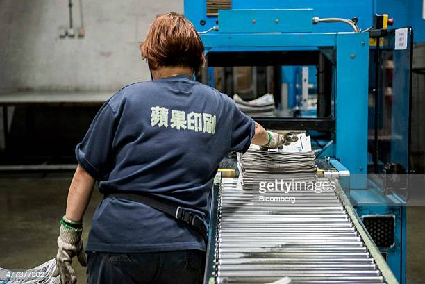 An employee collects copies of the Apple Daily newspaper published by Next Media Ltd at the company's printing facility in the Tseung Kwan O district...