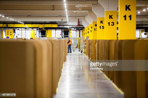 An employee collects customer purchase orders from storage bays ahead of packaging at the new Amazon Inc fulfilment center on its official day of...