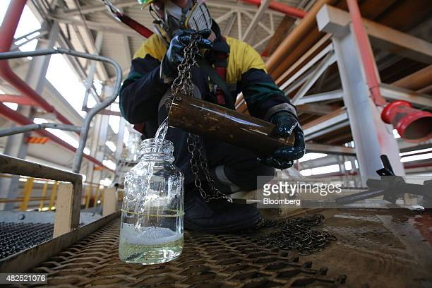 An employee collects fuel samples from a freight wagon for laboratory testing at the 'TANECO' refining and petrochemical plant operated by Tatneft...