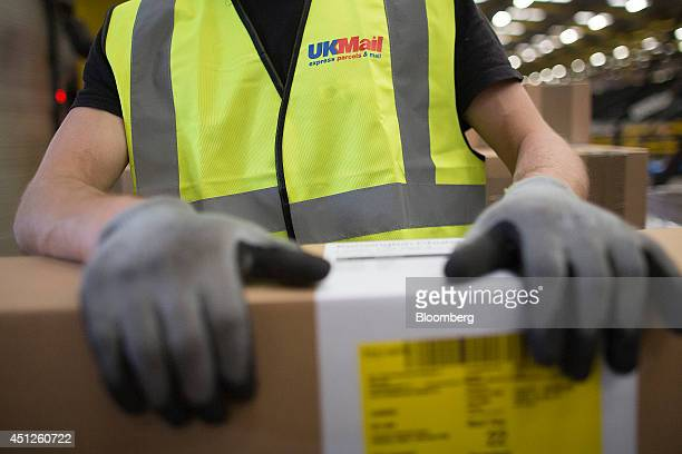 An employee collects packages ahead of loading for delivery at UK Mail Group Plc's letter and parcel sorting center in Birmingham UK on Thursday June...