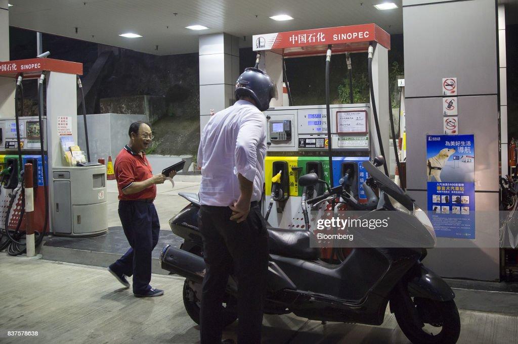 An employee collects payment from a customer after refueling a vehicle at a China Petroleum & Chemical Corp. (Sinopec) gas station at night in Hong Kong, China, on Tuesday, Aug. 22, 2017. Sinopec is scheduled to report second-quarter results on Aug. 25. Photographer: Vivek Prakash/Bloomberg via Getty Images