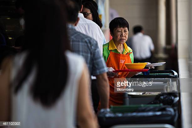 An employee collects used dishes at the Golden Shoe food center in Singapore on Tuesday Jan 6 2015 In a culture that traditionally expects children...