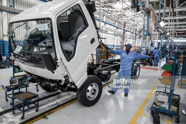 An employee controls a hoist to lift the cabin of an Isuzu NPR NSeries Truck on the assembly line inside the Isuzu East Africa Ltd plant in Nairobi...