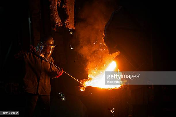 An employee controls molten iron as it pours from the furnace into a cauldron at AGA Rangemaster Plc's foundry in Coalbrookdale UK on Tuesday Oct 1...