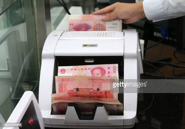 An employee counts 100-yuan notes at a bank in Nantong in China's eastern Jiangsu province on July 23, 2018. - China on July 23 rejected accusations...
