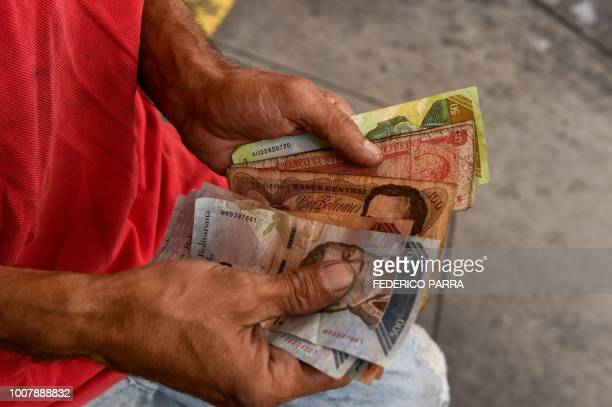An employee counts Bolivar bills at a gas station in Caracas on July 30 2018 Venezuelan President Nicolas Maduro announced fuel price regulations for...