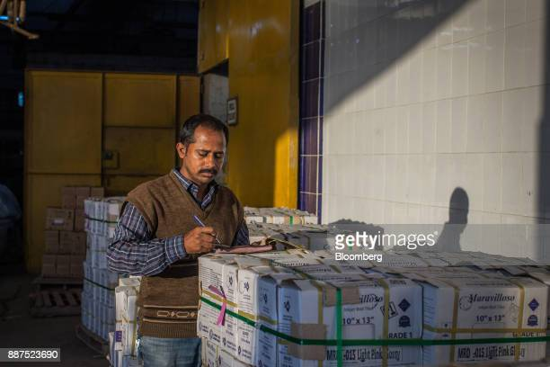 An employee counts boxes of tiles before delivery to the warehouse at the Shabbir Tiles Ceramics Ltd production facility in Karachi Pakistan on...