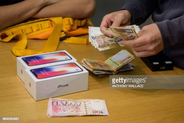 An employee counts cash at an Apple store as a customer buys two 10th anniversary iPhone X's in Hong Kong on November 3 2017 Apple profits soared by...