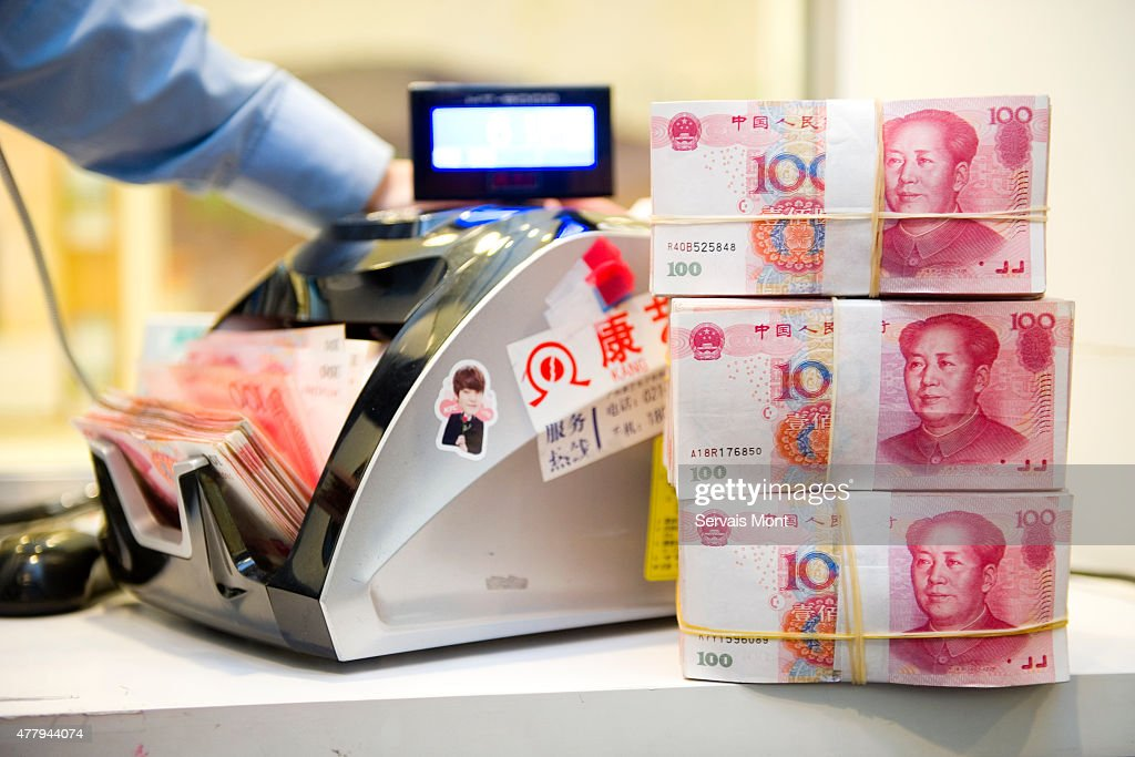 An employee counts Chinese Yuan bank notes in a Standard Chartered bank branch, on May 13, 2015, in Shanghai, China. Aiming for more access to the global financial market, China is encouraging the RMB or Renminbi as the Chinese Yuan is known in China (meaning 'the money of the people') to become more global.