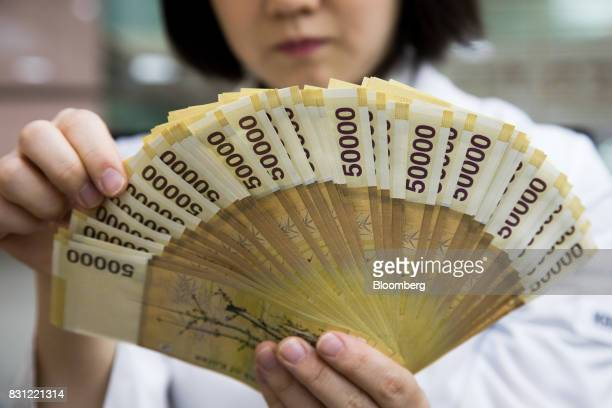 An employee counts genuine South Korean 50000 won banknotes in this arranged photograph at the Counterfeit Notes Response Center of KEB Hana Bank in...