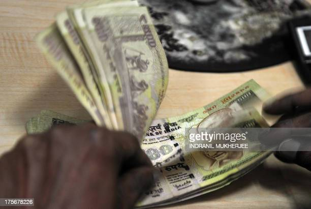 An employee counts Indian rupee notes at a foreign exchange dealer in Mumbai on August 6 2013 India's rupee plunged to a fresh record low against the...