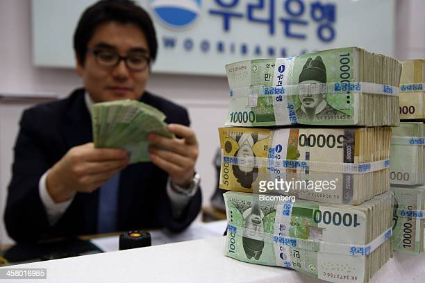 An employee counts South Korean 10000 won banknotes for a photograph behind stacked won banknotes at a Woori Bank Co branch in Seoul South Korea on...