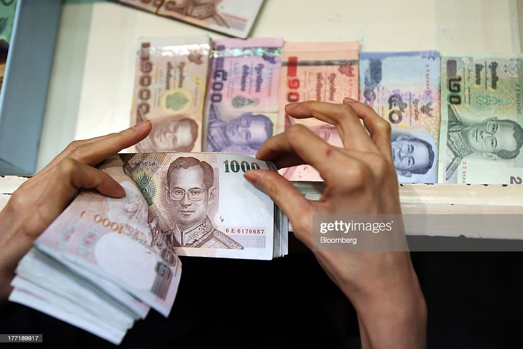 An employee counts Thai one-thousand baht banknotes as banknotes of other denominations sit inside a drawer at a Super Rich 1965 Co. currency exchange store in Bangkok, Thailand, on Thursday, Aug. 22, 2013. Thailand's baht fell to the weakest level since August 2010 after Federal Reserve minutes showed officials support a cut in stimulus this year should the U.S. economy improve. Photographer: Dario Pignatelli/Bloomberg via Getty Images