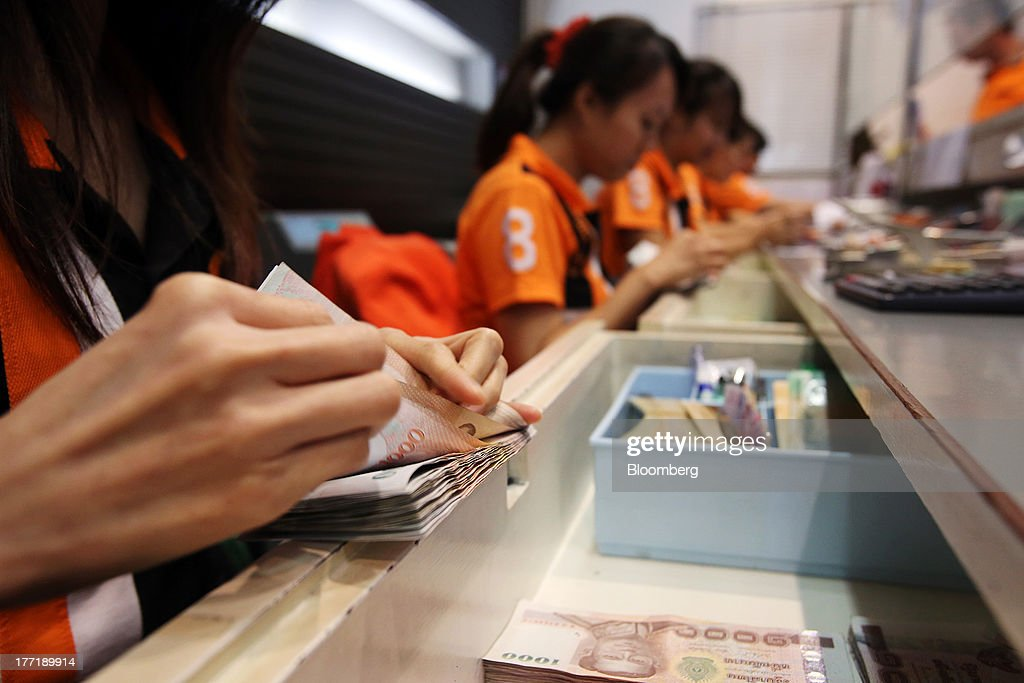 An employee counts Thai one-thousand baht banknotes at a Super Rich 1965 Co. currency exchange store in Bangkok, Thailand, on Thursday, Aug. 22, 2013. Thailand's baht fell to the weakest level since August 2010 after Federal Reserve minutes showed officials support a cut in stimulus this year should the U.S. economy improve. Photographer: Dario Pignatelli/Bloomberg via Getty Images