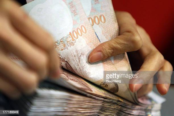 An employee counts Thai onethousand baht banknotes at a Super Rich 1965 Co currency exchange store in Bangkok Thailand on Thursday Aug 22 2013...