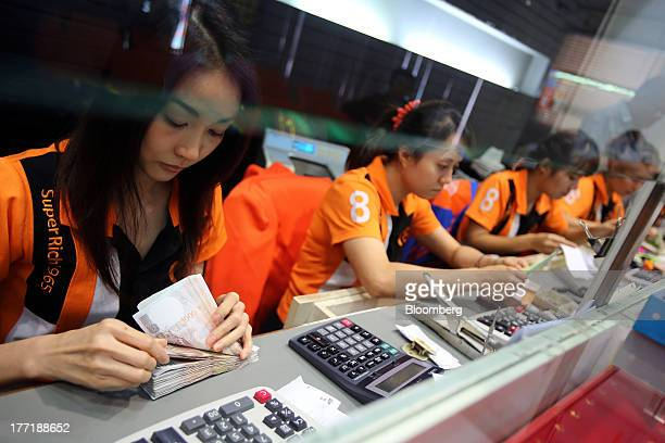 An employee counts Thai onethousand baht banknotes left at a Super Rich 1965 Co currency exchange store in Bangkok Thailand on Thursday Aug 22 2013...