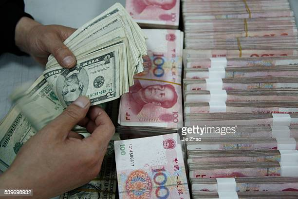 An employee counts the U.S. Dollars banknotes at a branch of the Industrial and Commercial Bank of China in Huaibei, Anhui province April 22, 2010....