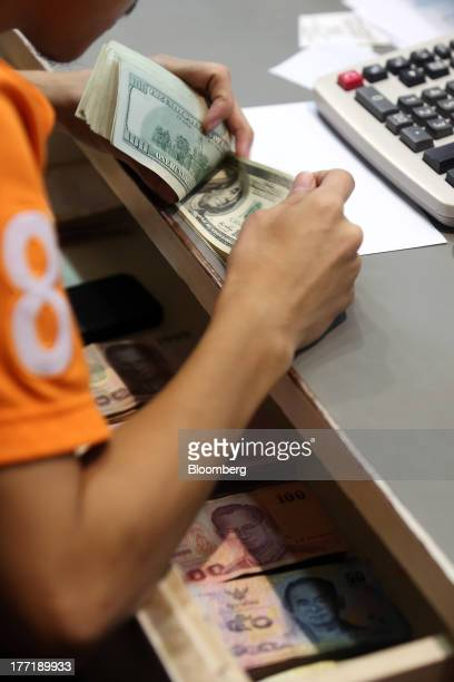 An employee counts US onehundred dollar banknotes as Thai baht banknotes sit inside a drawer at a Super Rich 1965 Co currency exchange store in...