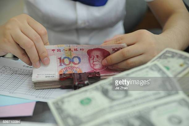 An employee counts Yuan banknotes at a branch of Bank of China in Hefei, Anhui province September 17, 2010. VCP