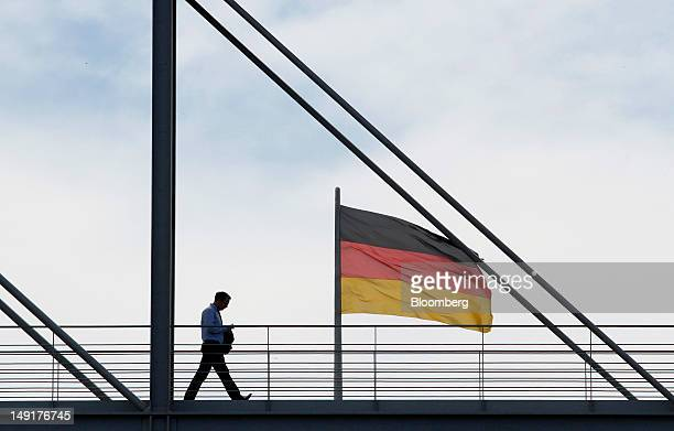 An employee crosses the bridge at the Reichstag, Germany's parliament building, in Berlin, Germany, on Tuesday, July 24, 2012. Chancellor Angela...