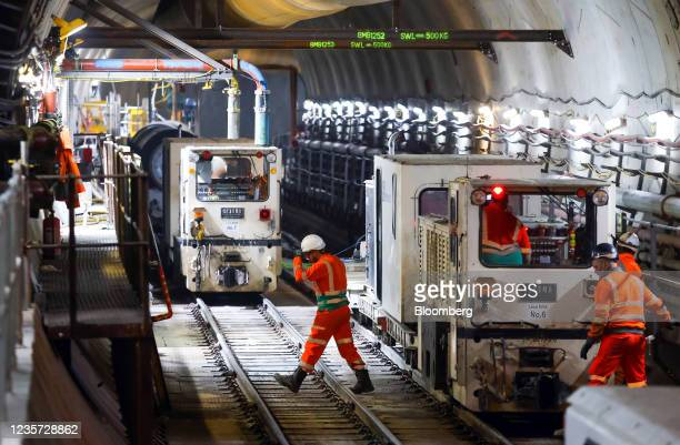 An employee crosses train tracks in the main tunnel at the Thames Tideway Tunnel super sewer construction project in London, U.K., on Wednesday, Oct....