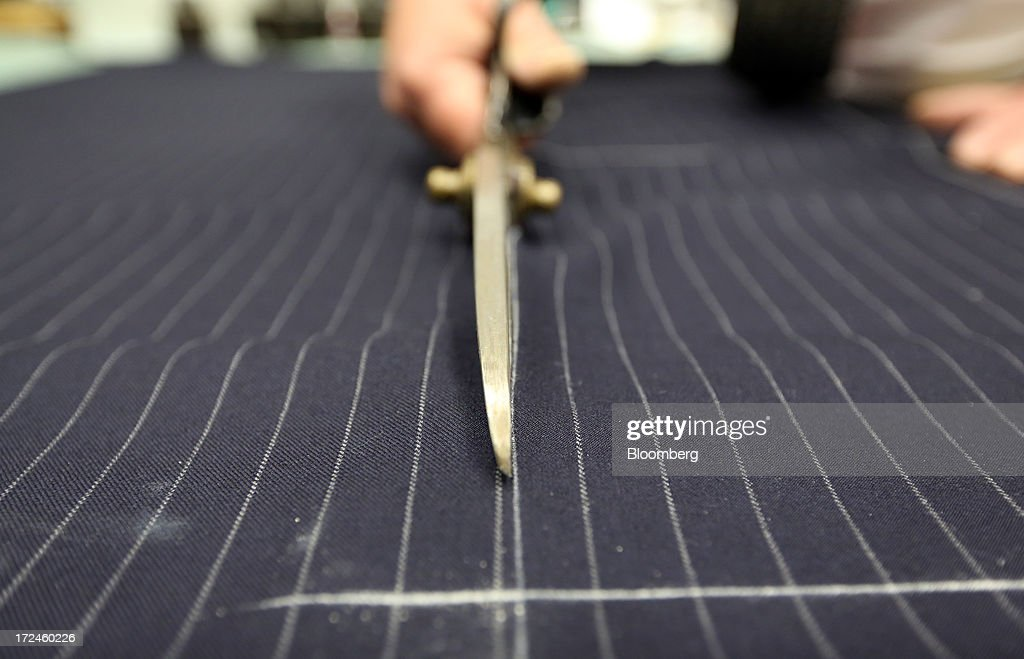 An employee cuts a piece of material for a suit in the workshop of the tailors Dege & Skinner based on Savile Row in London, U.K., on Tuesday, July 2, 2013. New orders at manufacturers rose for a fourth month in June, led by the textiles clothing industry, while input costs fell for a third month. Photographer: Chris Ratcliffe/Bloomberg via Getty Images