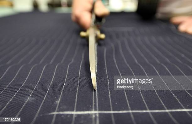 An employee cuts a piece of material for a suit in the workshop of the tailors Dege Skinner based on Savile Row in London UK on Tuesday July 2 2013...
