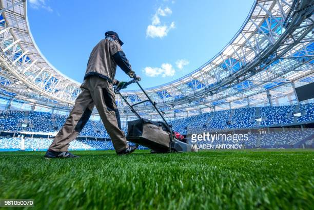 An employee cuts grass on the pitch of the Nizhny Novgorod Arena in Nizhny Novgorod on May 21 2018 Nizhny Novgorod stadium will host four group...