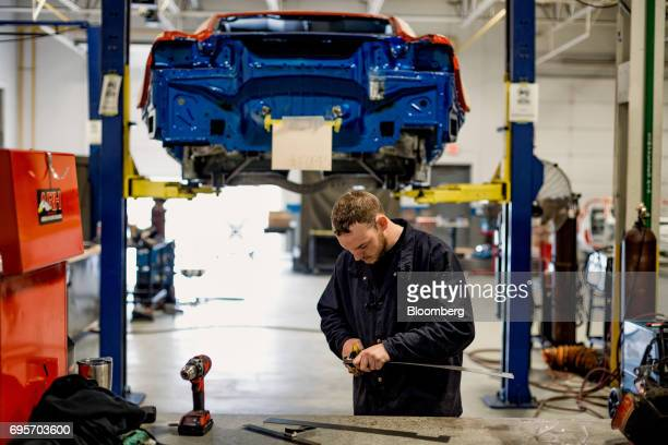 An employee cuts metal while working on a the chassis of a General Motors Co Chevrolet COPO Camaro performance vehicle at the company's build center...
