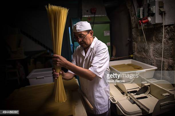 An employee cuts noodles at Pasta Sanmarti's factory on October 27 2015 in Caldes de Montbui Spain The Sanmarti family has been involved in the...