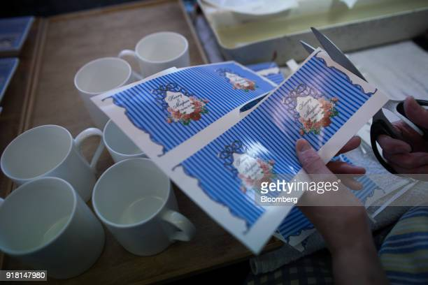 An employee cuts transfers to be used on china mugs to commemorate the wedding between Henry Windsor and Meghan Markle at Halcyon Days Ltd's factory...