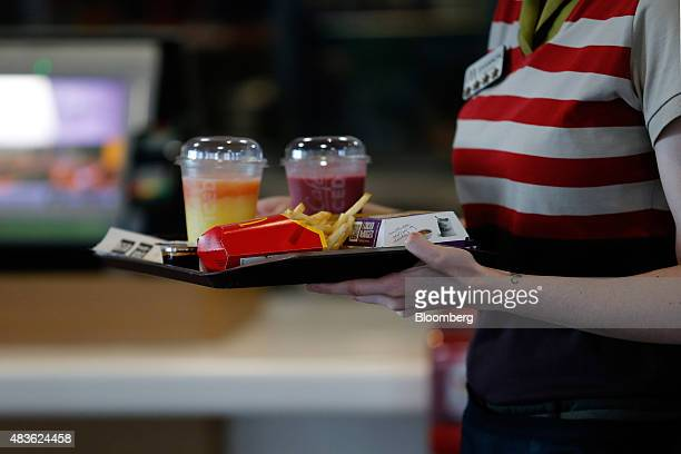 An employee delivers a tray of food and beverages to a customer's table inside a McDonald's Corp restaurant in Manchester UK on Monday Aug 10 2015...