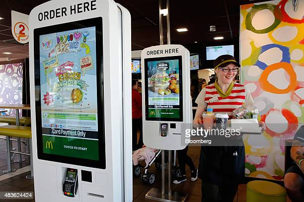 An employee delivers a tray of food and drinks to a customer's table inside a McDonald's Corp restaurant in Manchester UK on Monday Aug 10 2015...