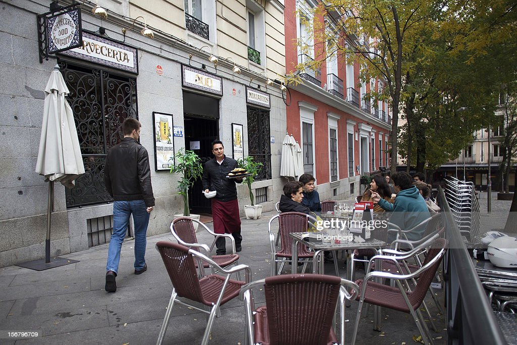 An employee delivers plates of food to customers sitting on an outdoor terrace outside a 100 Montaditos restaurant in Madrid, Spain, on Wednesday, Nov. 21, 2012. The Madrid-based chain in January opened its first U.S. restaurant in Miami and aims to have eight outlets in Florida by next March. Photographer: Angel Navarrete/Bloomberg via Getty Images