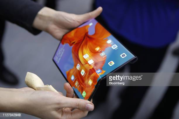 An employee demonstrates a Mate X foldable 5G mobile device at the Huawei Technologies Co pavilion on the opening day of the MWC Barcelona in...