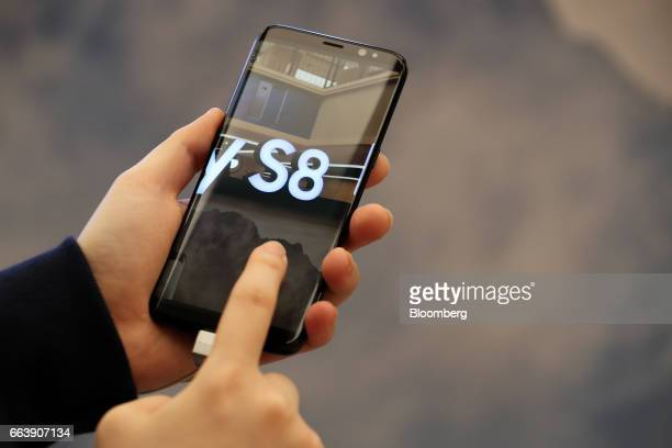 An employee demonstrates a Samsung Electronics Co Galaxy S8 smartphone at one of the company's promotional booths in Seoul South Korea on Sunday...