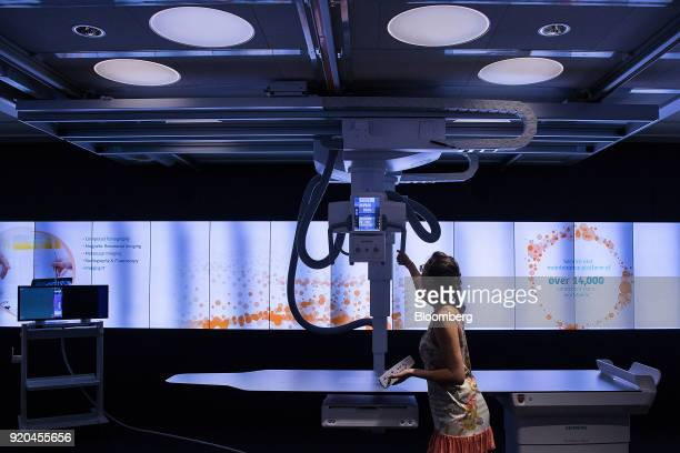 An employee demonstrates a Siemens Multitom Rax Xray scanner inside the Siemens AG Healthineers showroom in Forchheim Germany on Wednesday July 19...