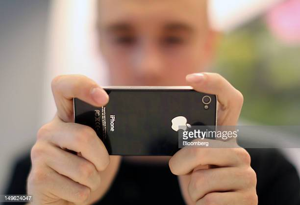 An employee demonstrates an Apple Inc iPhone 4S inside a reStore a premium Apple product reseller in Moscow Russia on Wednesday Aug 1 2012 OAO Mobile...