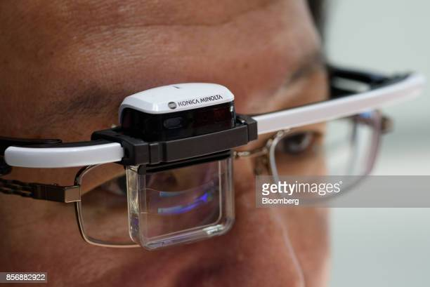 An employee demonstrates Konica Minolta Inc's Wearable Communicator at the company's booth at the CEATEC Japan 2017 exhibition in Chiba Japan on...