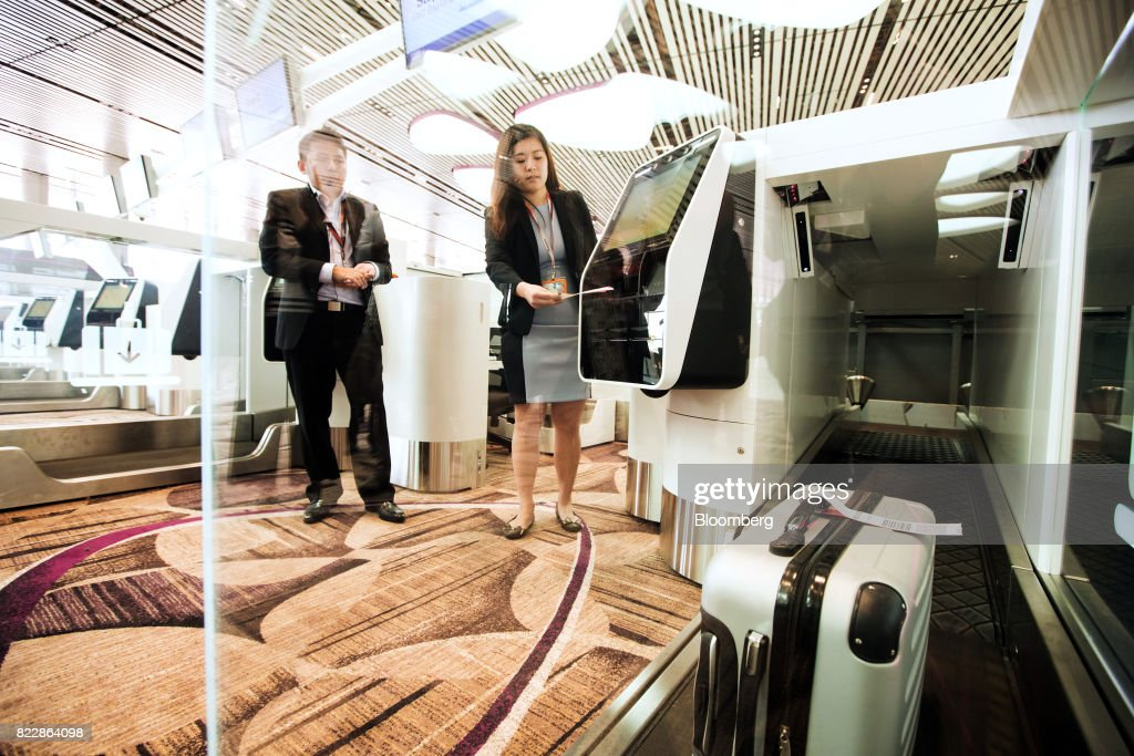 An employee demonstrates the automated luggage check-in system during a media preview of the new Terminal 4 (T4) at Changi Airport in Singapore, on Tuesday, July 25, 2017. The terminal which will open later this year, will feature an array of fast and seamless travel (FAST) technologies to speed people-processing without the need for human supervision, from face-recognition software to automated bag-tagging and checking. Photographer: Nicky Loh/Bloomberg via Getty Images