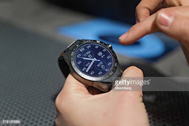 An employee demonstrates the functions of a 'Connected' luxury smartwatch produced by TAG Heuer International SA at the company's booth during the...