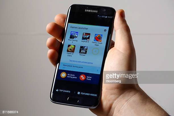 An employee demonstrates the new Samsung Electronics Co Galaxy S7 edge with 3D thermo forming which shows the new software 'Game Launcher' page in...