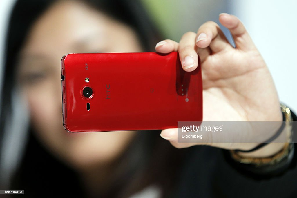 An employee demonstrates the picture quality of the HTC J Butterfly smartphone, produced by HTC.Corp., during the unveiling event in Tokyo, Japan, on Tuesday, Nov. 20, 2012. Taiwan's HTC Corp. needs to improve its global brand awareness to gain share in China, and its newly unveiled model is likely to help the vendor do that. Photographer: Kiyoshi Ota/Bloomberg via Getty Images