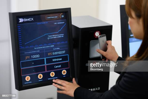 An employee demonstrates the usage of a bitcoin automated teller machine at the BITPoint Japan Co headquarters in Tokyo Japan on Thursday May 25 2017...